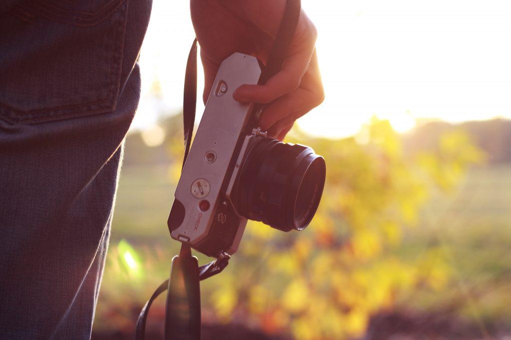 person holding bridge camera during daytime